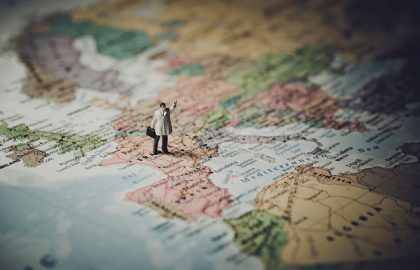 Miniature businessman on map of Europe. Color tone tuned